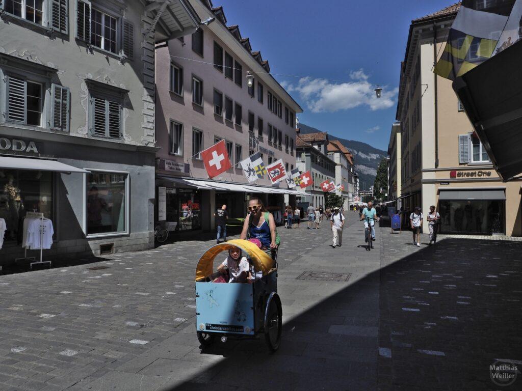 Beflaggte Fußgängerzone Chur mit Lastenkinderrad