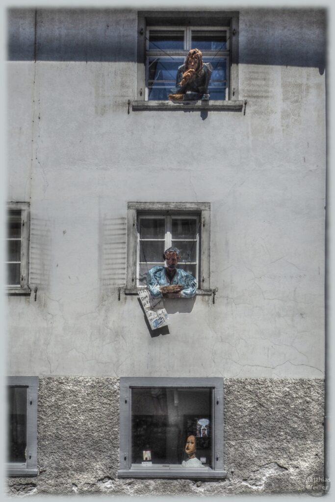 Zerknitterte Schauskulpturen an Fenstern, verwittert