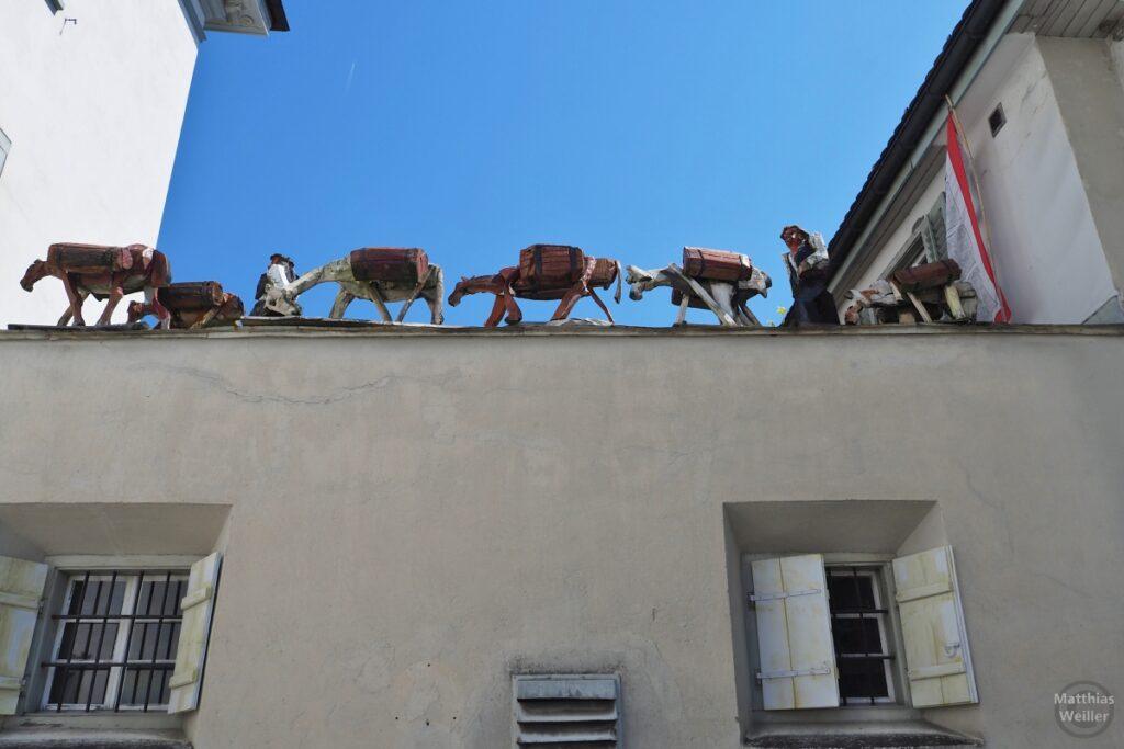 Skulpturenzug von Maultieren auf Hausdachkante