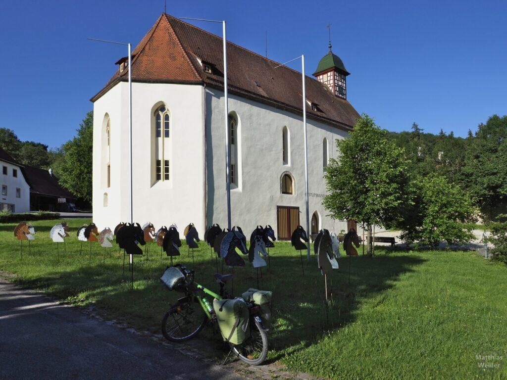Kapelle mit Fachwerktürmchen, grünes Reisevelo, Pferdekopfstelen