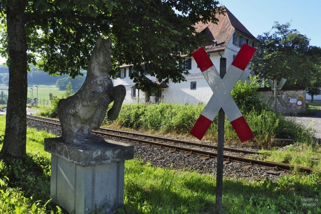 Steinskulptur Pferd neben Andreaskreuz, Bahntrasse, Gestütsgasthof versteckt dahinter