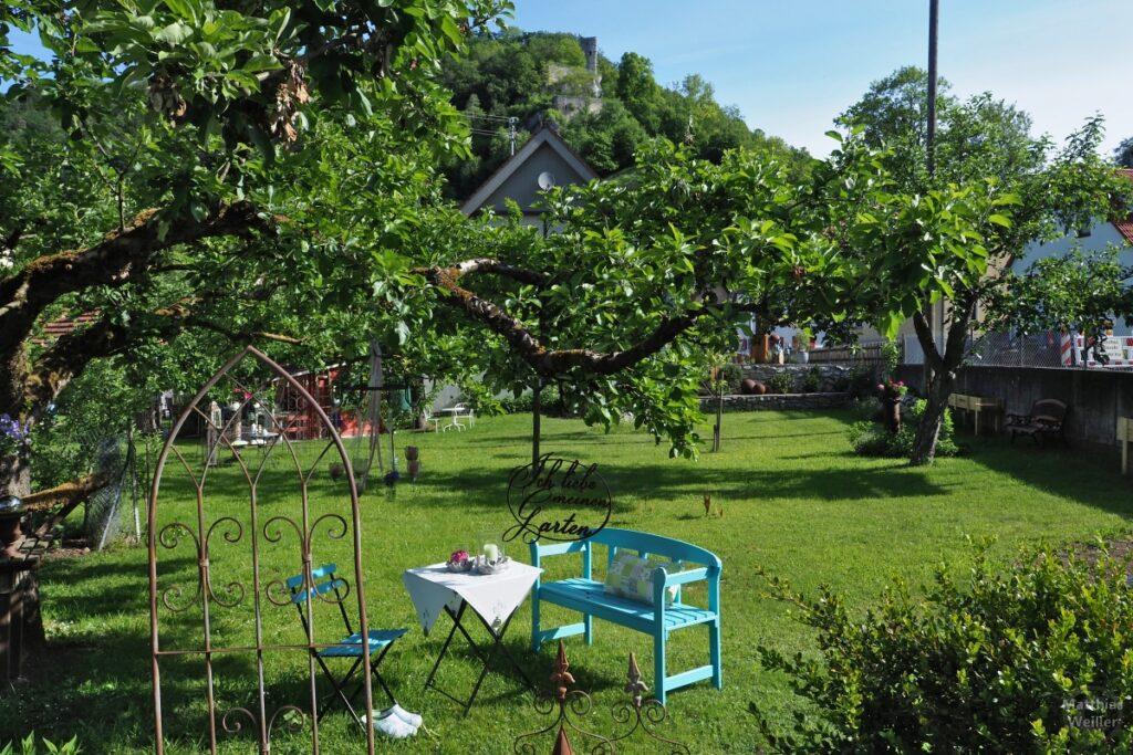 Bunter Garten mit blauer Bank, dekoriertem Tisch vor Burgruine Hundersingen