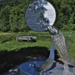 """Metallglänzende Forellenskulptur mit runder Infotafel """"Lauterzeichen"""""""