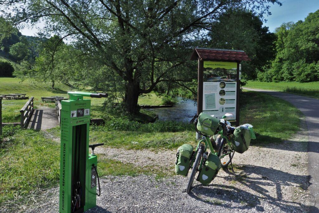 Fahrradreparaturstation grün mit grünem Resievelo, Infotafel, Picknickecke und Lauter