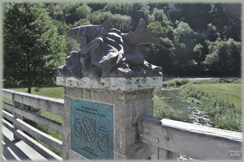 Fischskulptur über Stein auf Brücke