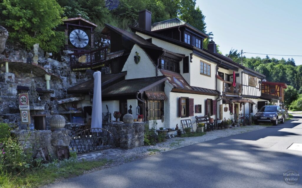 Haus vor Felswand mit Fachwerk, alter Holzuhr