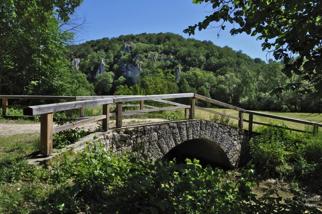 Steinbogenbrücke mit Holzgeländer und Felszapfenkulisse im Hintergrund