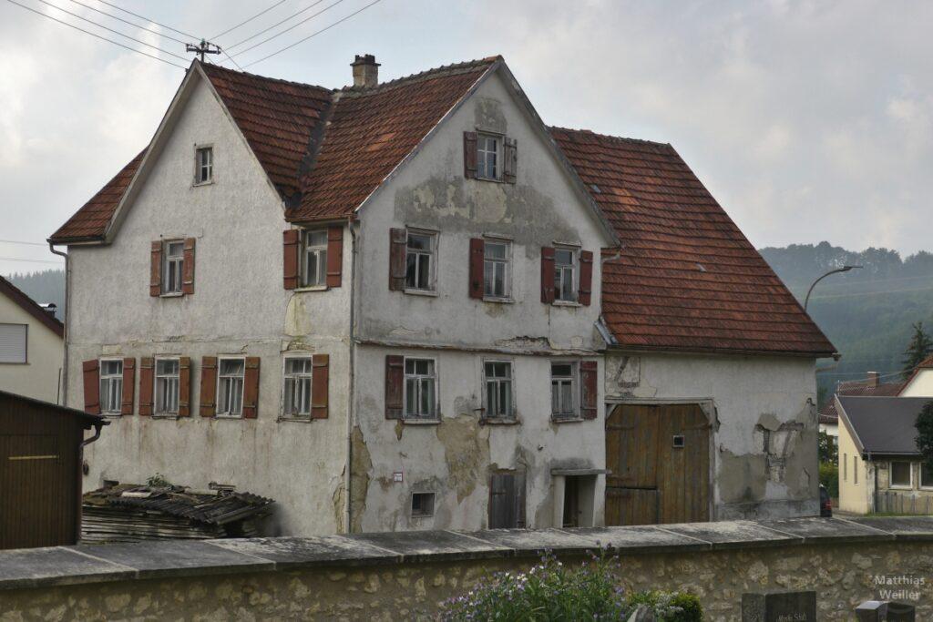 Verfallenes Haus mit braunen Läden