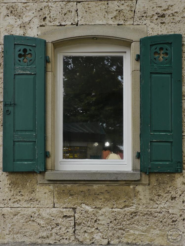 Morbides Fenster mit grünen Läden