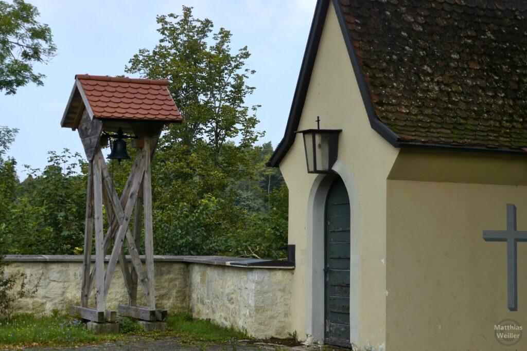 Holzgerüst mit Glocke und Ziegeldach nebn Kapelleneingang