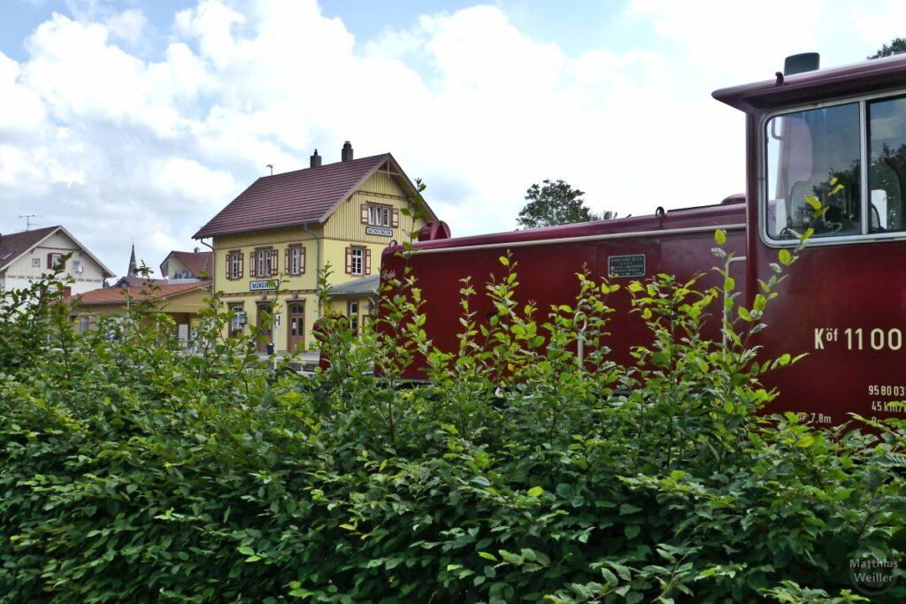 Bahnhof Münsingen mit Rangierlock im Ausschnitt vorne, über grüne Hecke gesehen