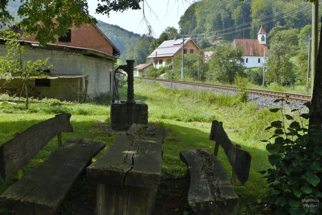 Verwitterter Picknickplatz mit alter Pumpe vor Kapelle mit Häusern und Bahntrasse in Sondernach