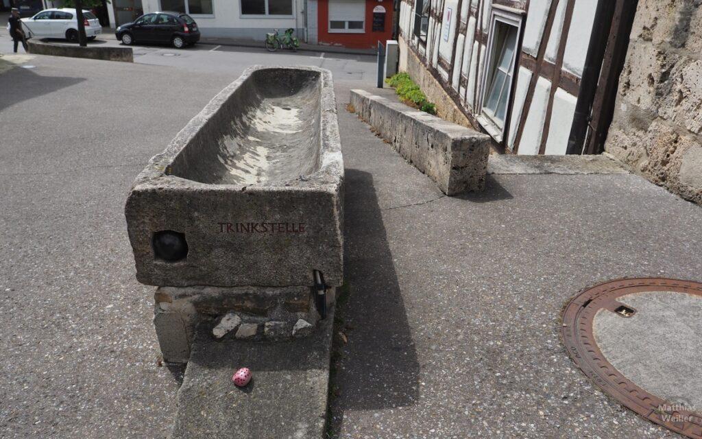Steinwanne, historische Trinkstelle, mit gepunktem rosa Stein