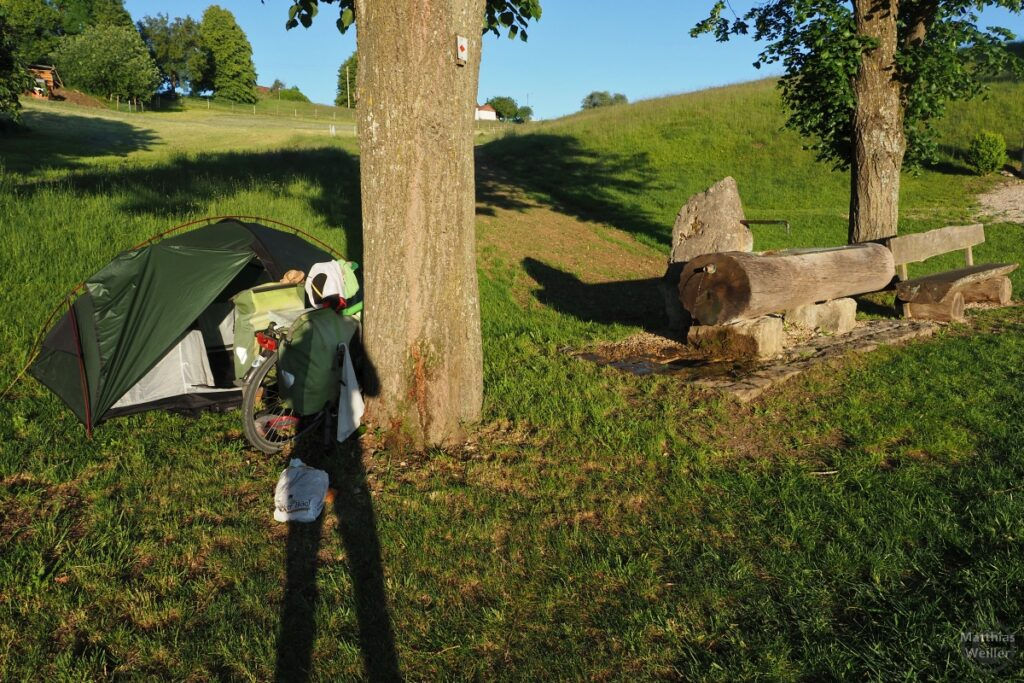Zelt, Velo, Brunnen mit Holzstammwanne, Holzbank