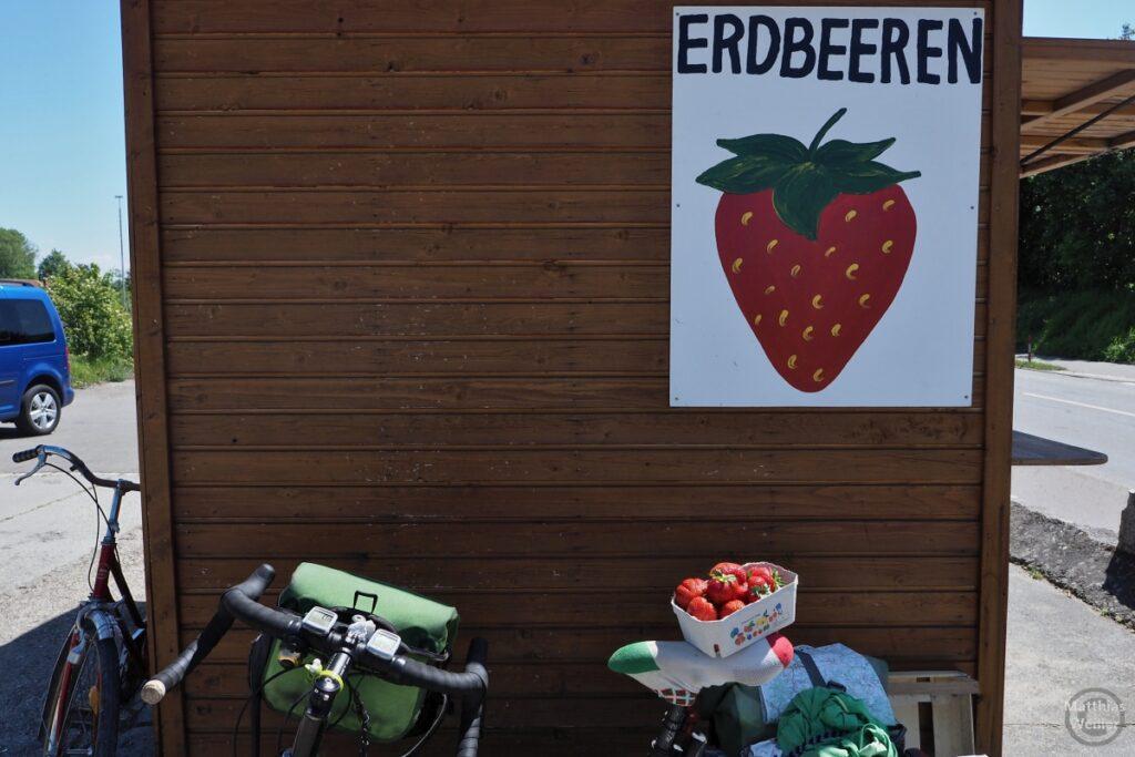 """Velo mit Erdbeerkörbchen auf dem Sattel vor Hütte """"Erdbeeren"""" mit gemalter Erdbeere"""