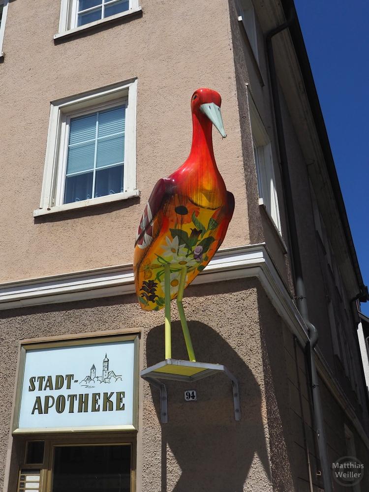 "Rot-bunte Storchenskulptur an Hauswand neben Schild ""Stadtapotheke"""