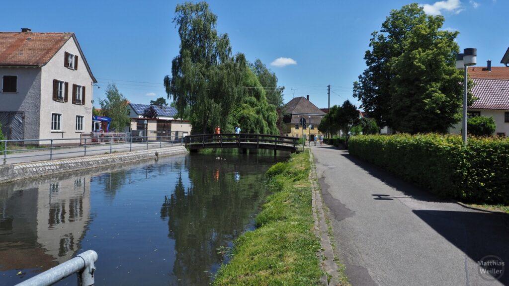 Kanalisierte Ablach in Mengen mit gebogener Holzbrücke