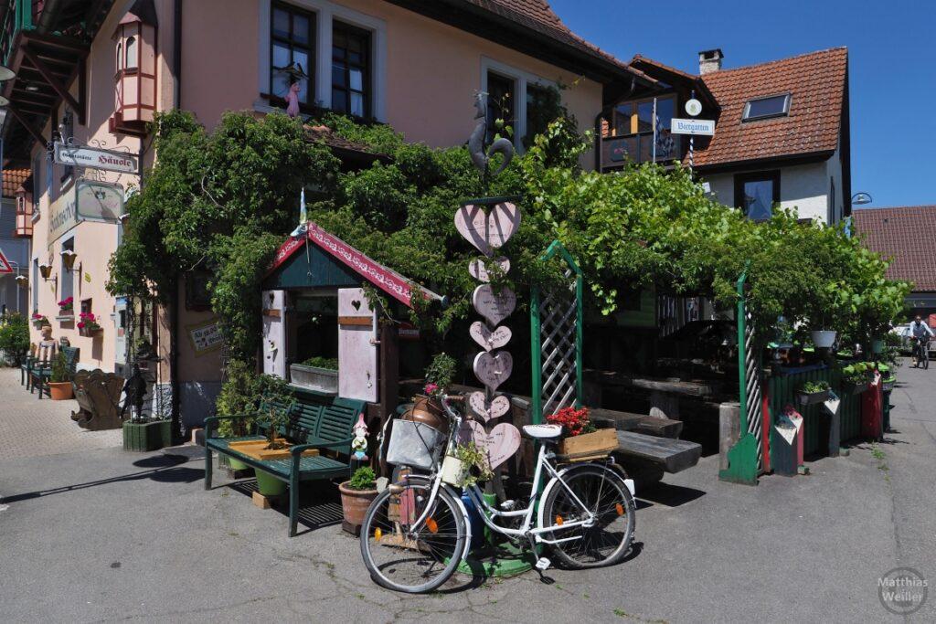 Sitzlaube an Eckhaus mit Herzmobile und Blumenschmuckvelo