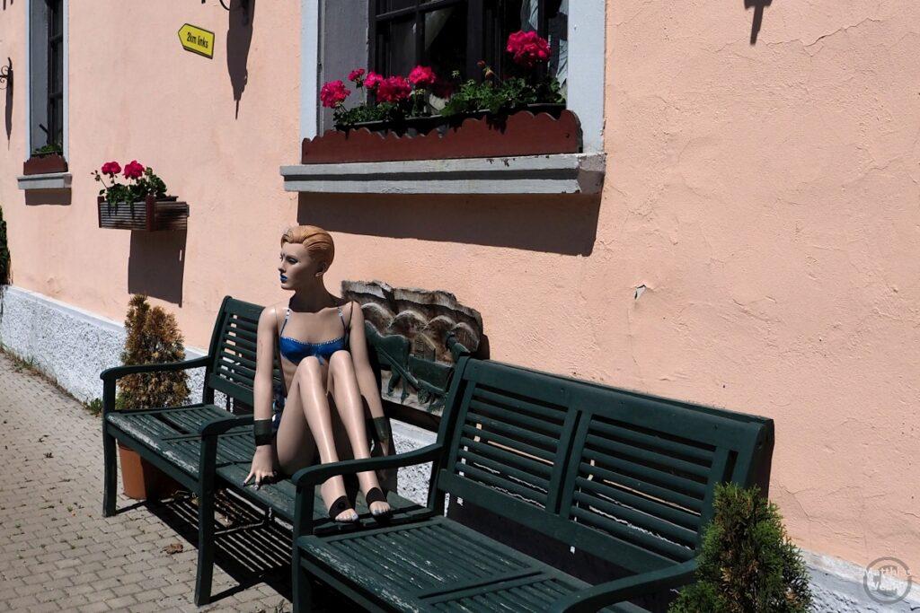 Badenixe als Puppe auf grüner Bank vor Hauswand mit Geranienfenster