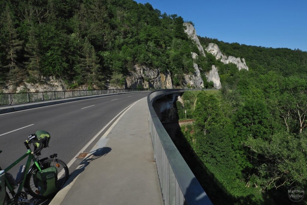 Brückenflucht an Donau mit Geländer, über Eisenbahntrasse, mit Kalkfelsen, mit grünem Reisevelo