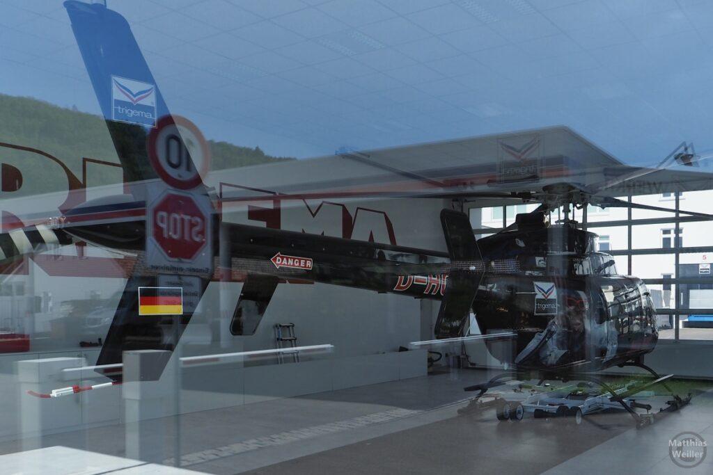 Trigema-Hubschrauber in Flughalle, Trigema-Affe gespiegelt