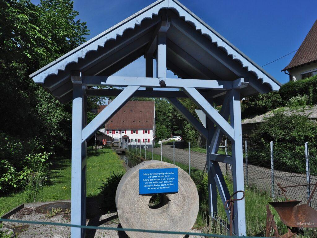 Mühlstein unter blauem Holzgiebelbaldachin