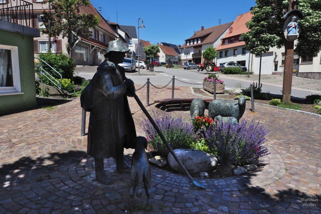 Skulptur Schäfer mit Schafen und Blumen an Pciknickecke neben Straße im Ort Obernheim