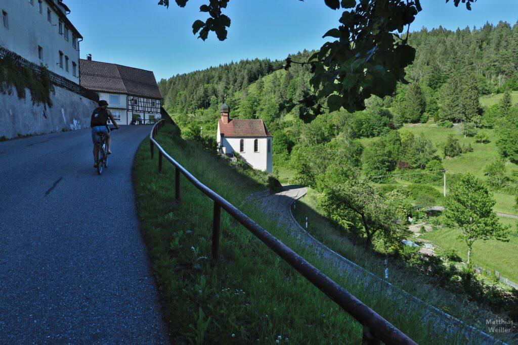 Auffahrt nach Mühlheim über Tal, mit Kapelle, Radlerin