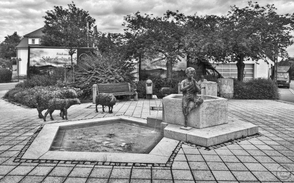 Brunnen mit Skulpturen von Flötenspieler und Schafen, schwarz/weißn