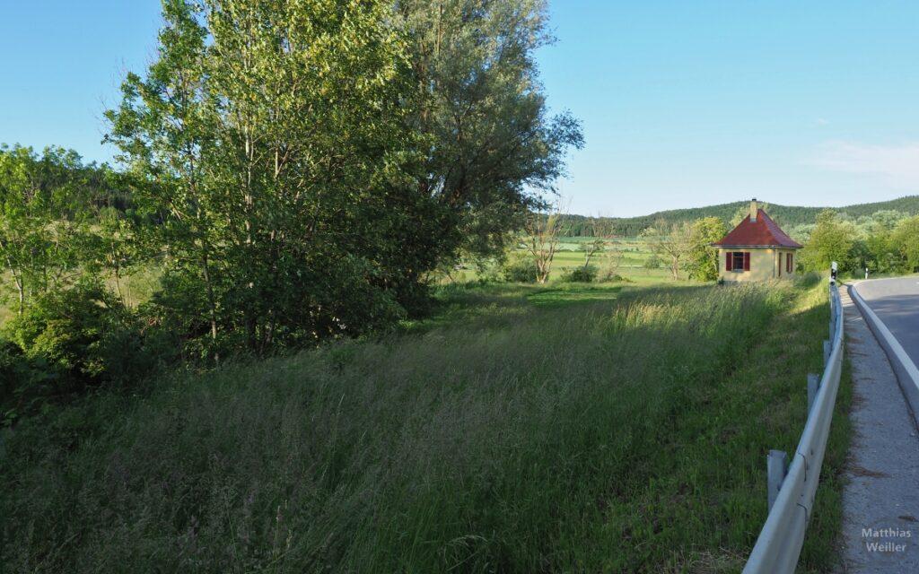 Weite Lauchertaue mit Häuschenhütte neben Leitplanke
