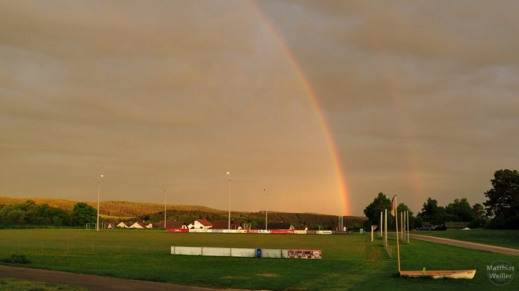 Regenbogen über Sportplatz, zweigeteilter Himmel hell/dunkel