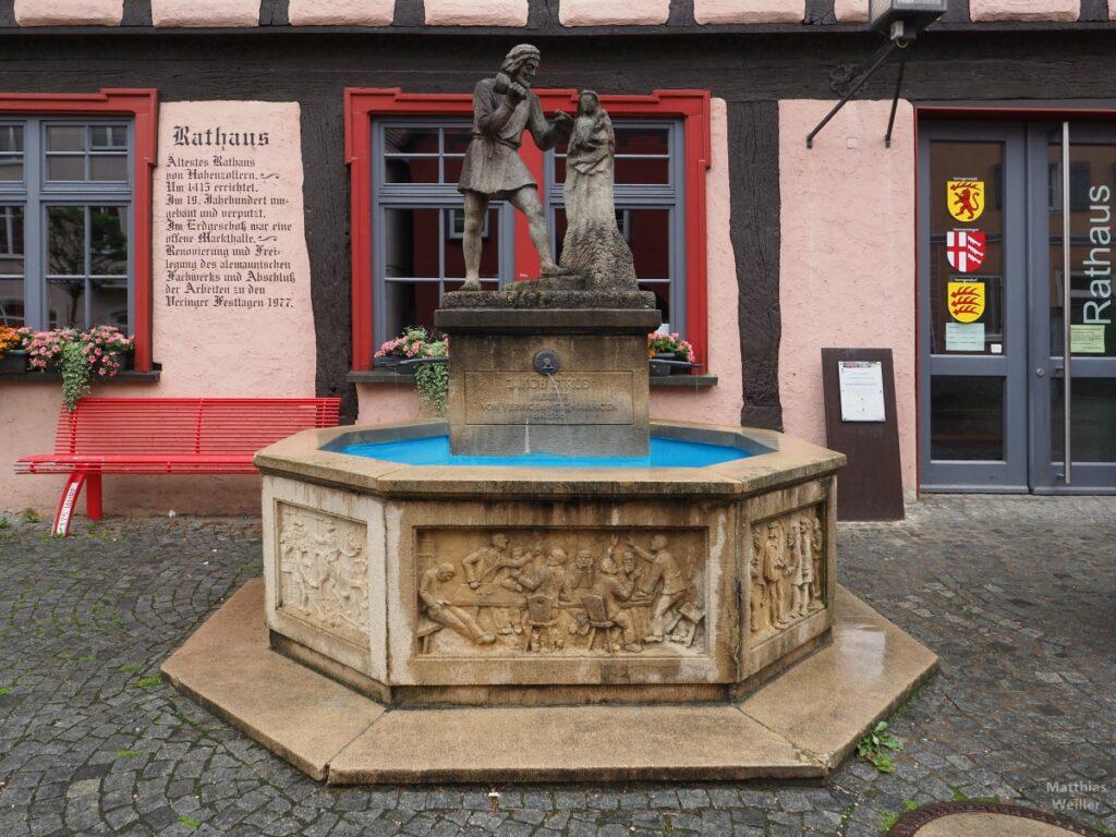 Brunnen mit Steinmetzskulptur vor Fresko Rathaus-Info