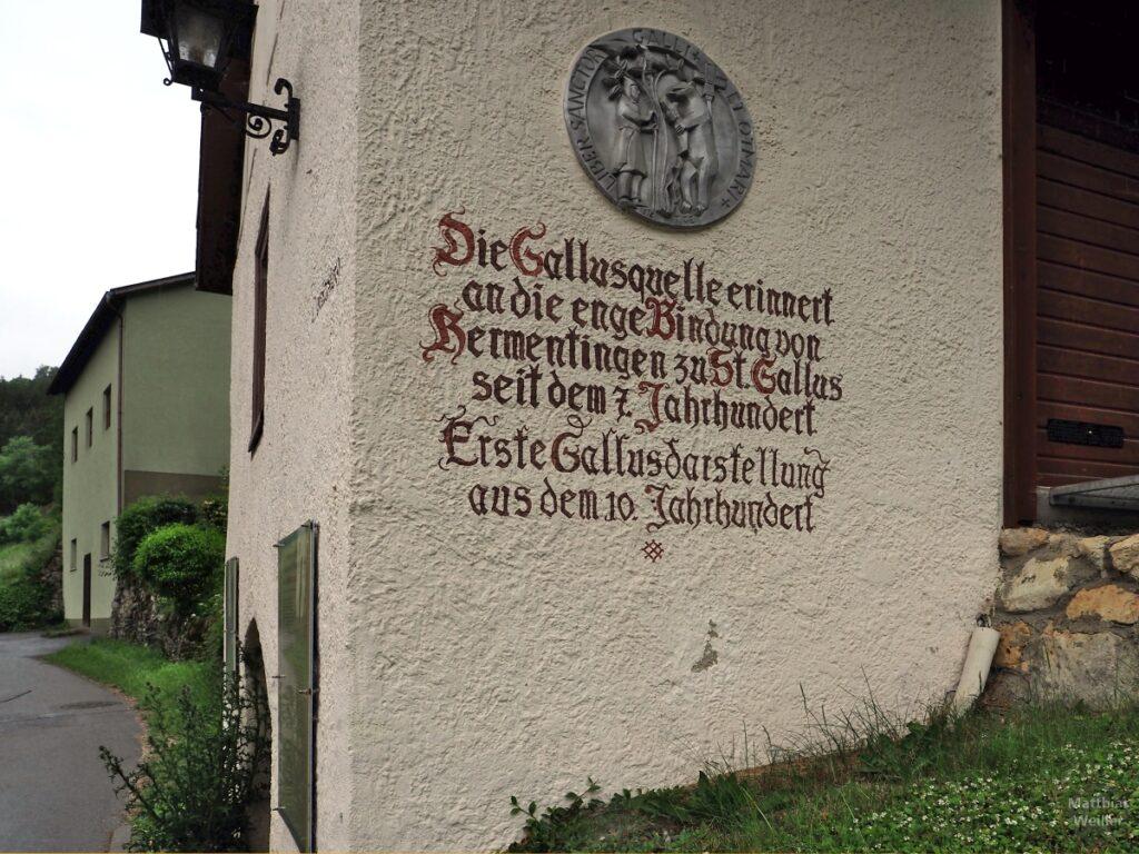 Schriftzug auf Hausfassade zur Gallusquelle mit St.-Gallus-Darstellung als Tellerdarstellung