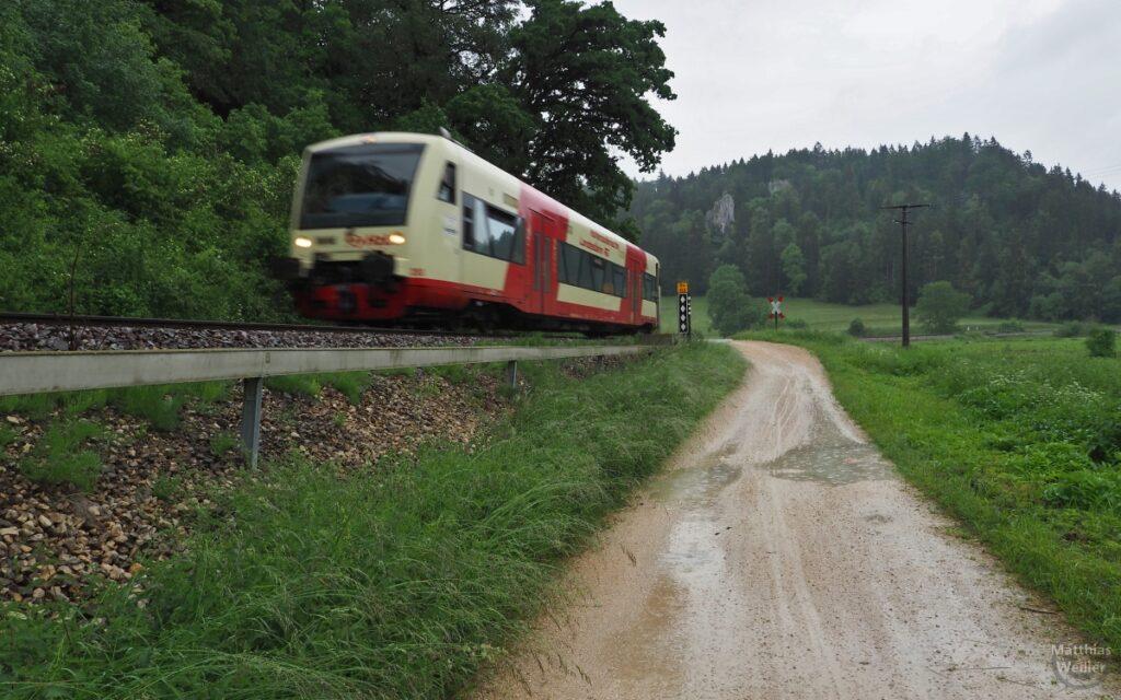 Triebwagen Hohenzollernbahn neben Fahrweg mit Regenpfützen