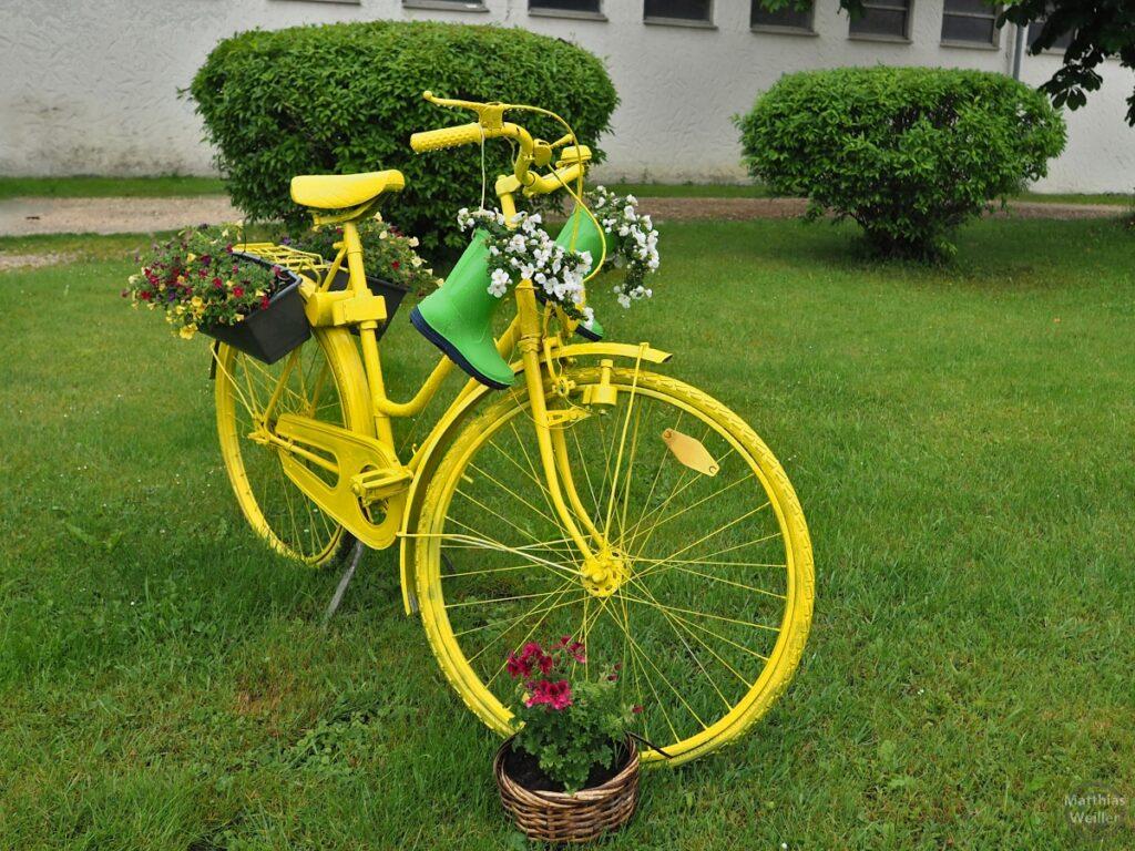 Gelb bemaltes Velo mit Blumen und grünen Gummistiefeln im Regen