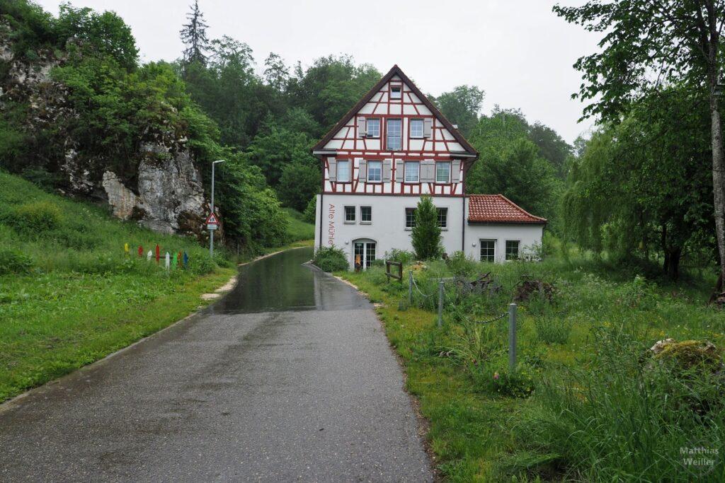 Straße zwischen Fels und Fachwerkhaus Alte Mühle