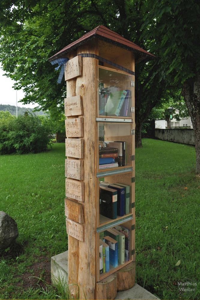 Naturholzturm als öffentliches Bücherregel mit Ziegeldach