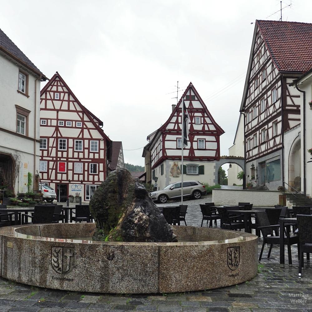 Brunnen mit Naturstein, Wappen Trochtelfingen, vor Fachwerkkulisse