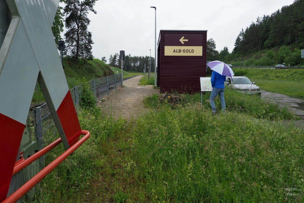 "Haltestelle ""Alb-Gold"" mit Person mit Regenschirm, Andreaskreuz"